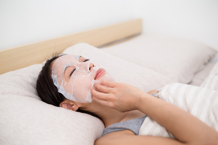 Woman lying down in bed with paper mask