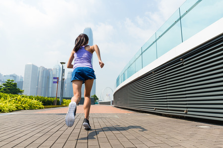 get a workout: The back view of woman running Stock Photo