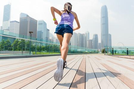 香港で走っている女性の後ろ姿 写真素材