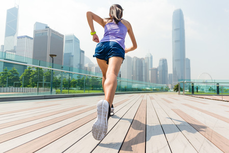 The back view of woman running in Hong Kong Stock Photo