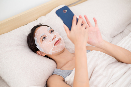 skincare facial: Woman using the cellphone with facial mask in bed