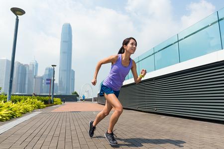 get a workout: Woman running in Hong Kong city
