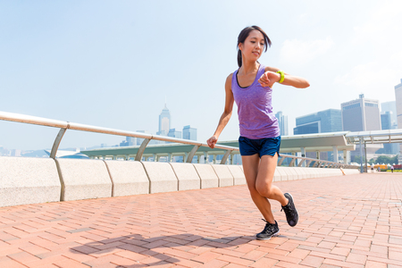 get a workout: Woman checking the record of running Stock Photo