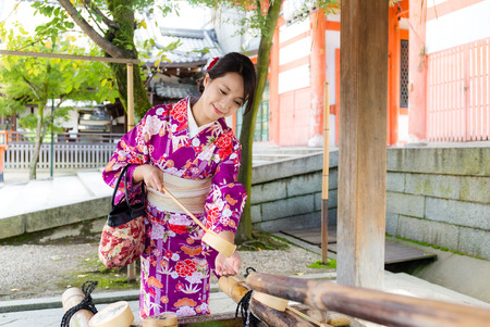 purification: Japanese woman using the water bamboo ladle for purification