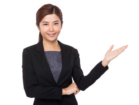 Empresaria joven con la mano que muestra la muestra en blanco Foto de archivo - 48346736