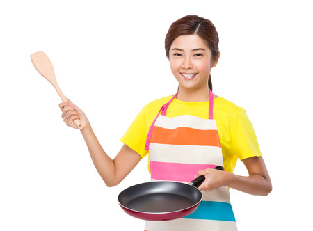 pan asian: Asian housewife using pan and wooden ladle Stock Photo