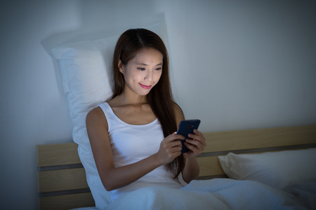 Woman use of the cellphone and sitting on bed