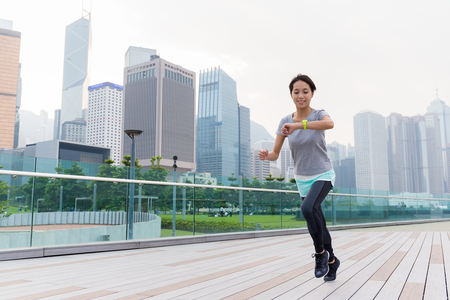 jogging track: Woman look at her wearable when running Stock Photo