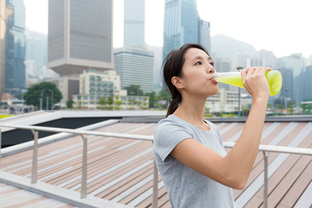 girl in sportswear: Asian Young Woman drinking with detox vegetable beverage at outdoor Stock Photo