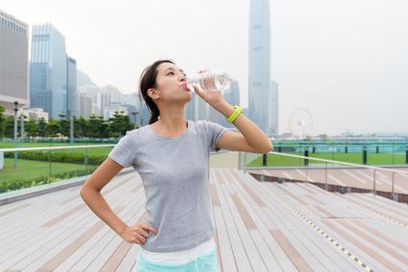 Frau trinken mit Wasser nach dem Laufen