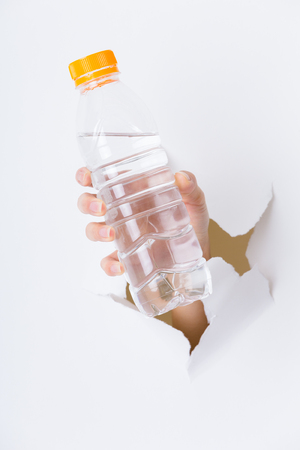 gash: Hand through the hole in paper with plastic bottle Stock Photo