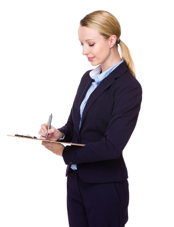 american banker: Caucasian Young Businesswoman write on clipboard Stock Photo