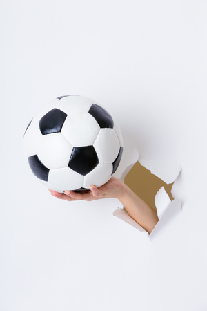 gash: Hand through the hole in paper with soccer ball