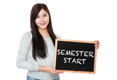 semester: Young woman hold with chalkboard showing semester start on board