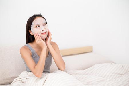 Vrouw doet de papieren masker op bed Stockfoto