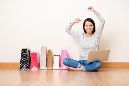 ノート パソコンを使用してオンライン ショッピングの興奮したアジア女性