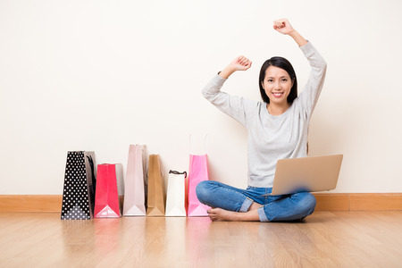 christmas shopping bag: Excited Asian Woman using the notebook computer for shopping online Stock Photo