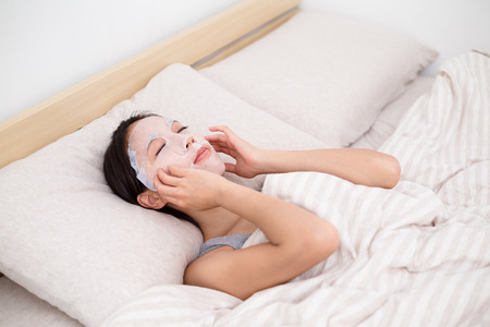 bed sheet: Young Woman use of the mask on bed