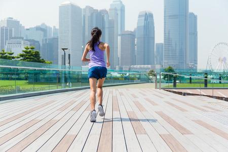 hacer footing: La vista trasera de la chica de jogging