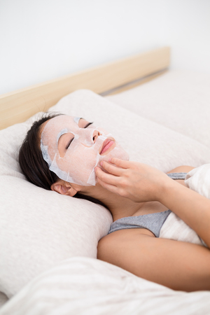 female mask: Asian Young Woman having paper mask on bed Stock Photo