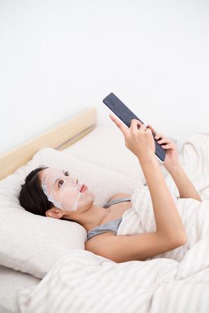 adn: Mujer que se acuesta con el uso de máscara facial tablet pc adn