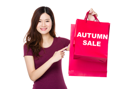 t off: Asian woman with finger point to shopping bag and showing autumn sale