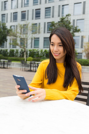 niñas chinas: Young Woman use of the smart phone at outdoor coffee shop