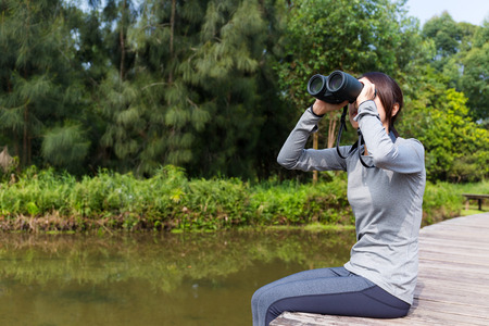 though: Asian woman watching though binoculars and sitting besides revier