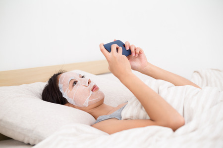Woman playing game with smartphone in bed when using the paper mask
