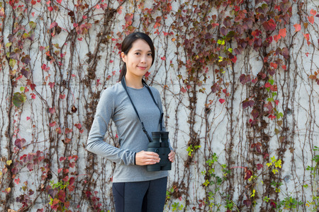 autumn young: Asian woman with binoculars over ivy wall