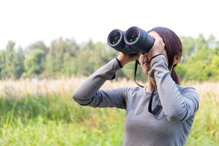 though: Asian Young woman watching though binoculars