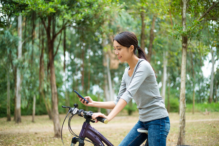 go for: Woman go for cycling and use cellphone Stock Photo