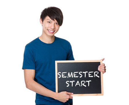 semester: Asian man with the blackboard showing phrase of semester start