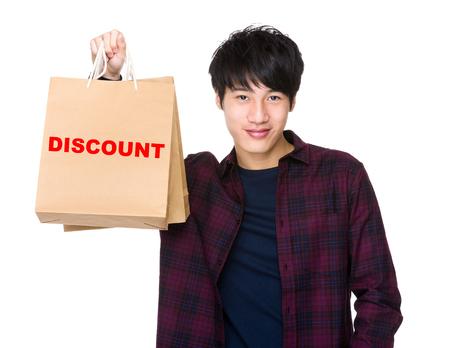 shopper: Happy Asian man shopper holding shopping bag for showing a word discount