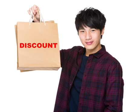 t off: Asian Man hold with shopping bag and showing a word discount