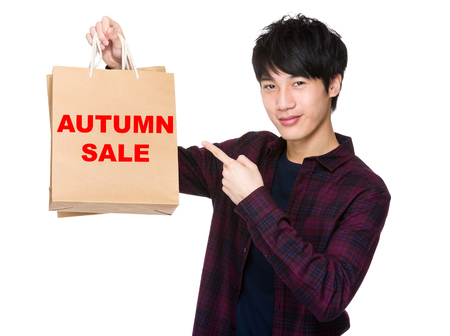 shopper: Happy young shopper with finger point to paper bag for showing phrase of autumn sale
