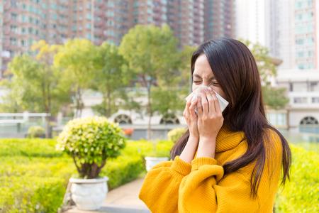 estornudo: estornudo de la mujer joven en al aire libre
