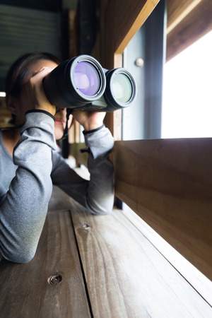though: Woman looking though binocular at wooden house