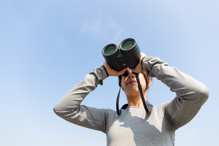 though: Young Woman looking though binoculars with clear blue sky Stock Photo
