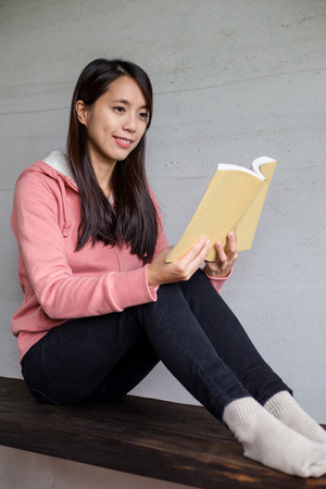 revise: Woman reading book at home