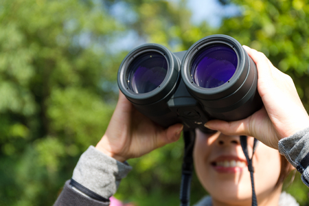 though: Woman looking though binoculars at forest