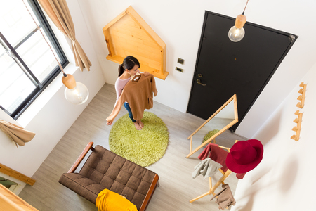 furniture home: Top view of woman holding clothes and standing infront of mirror