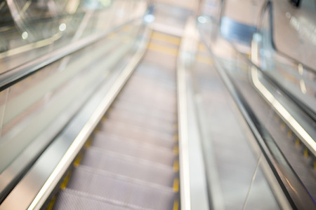 view of a staircase in a shop: Blurred escalator background