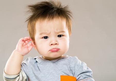 Confused baby boy hand touch ear Foto de archivo