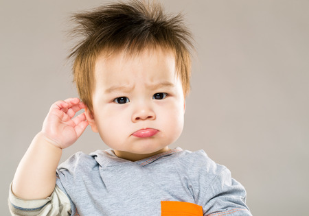 face shot: Confused baby boy hand touch ear Stock Photo