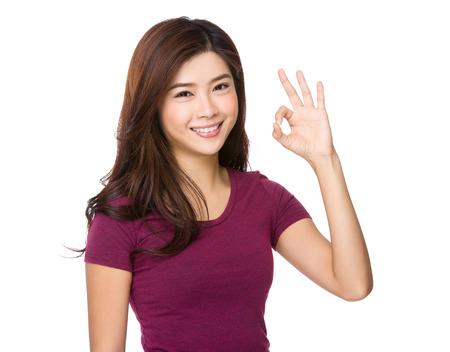 Asiatische Frau mit ok Zeichen Geste