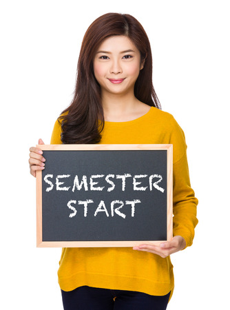 phrase: Woman with chalkboard showing phrase of semester start