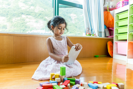 Little girl play tablet pc at her toy room