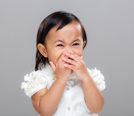 cover mouth: Happy girl with hand cover her mouth Stock Photo