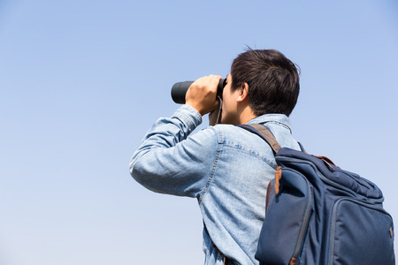 though: Man looking though the binocular against blue sky